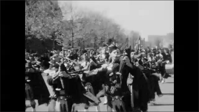 1930s: Men parade down the street, play bagpipes, drums.