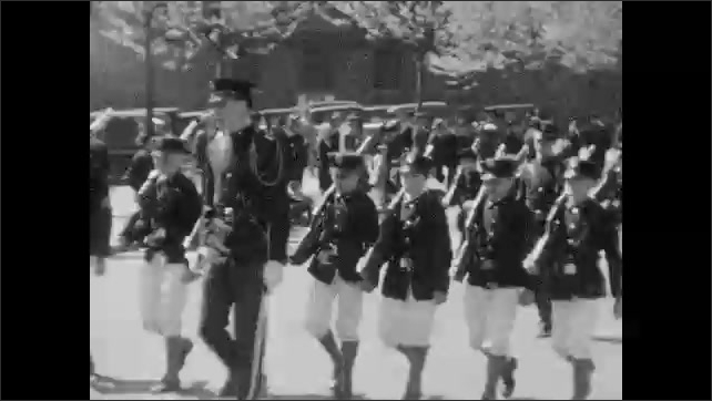1930s: Marching band parades down street. Children parade down street.