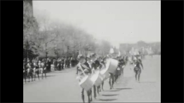 1930s: Marching band parades down street.