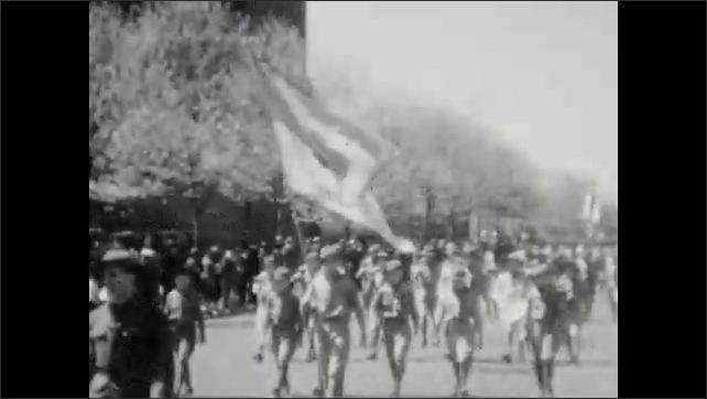 1930s: Children parade down street.
