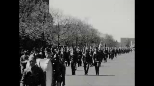 1930s: Children in uniform march down street. Marching band parades down street.