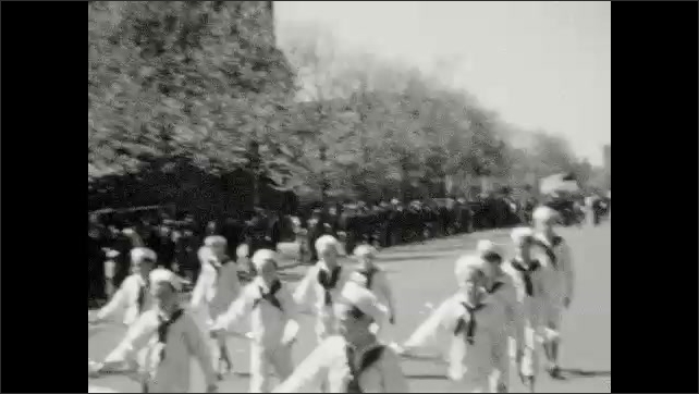 1930s: Marching bands parade down street.