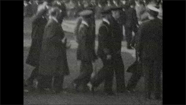 1930s: Men in suits and military uniforms walk by. Men salute. Men play baseball. Men box.