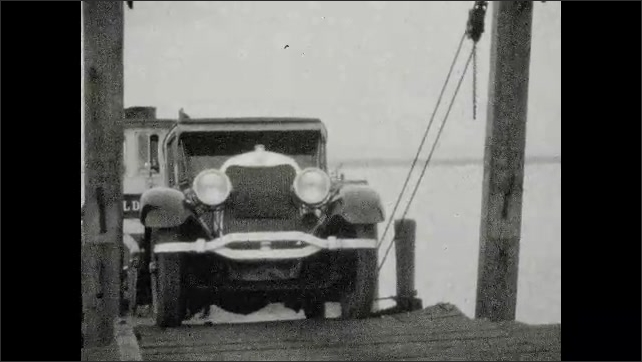 1920s: UNITED STATES: Car and man on Hildegard ferry. Car drives off ferry. Lady on porch by lake.