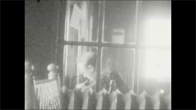 1920s: UNITED STATES: man and girl indoors. Hostel accommodation. Man seen through window of business. View along road.