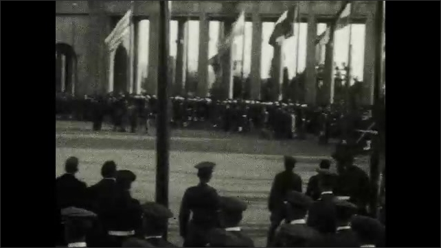 1920s: Canon is fired. People stand in formation around courtyard with flags flying.