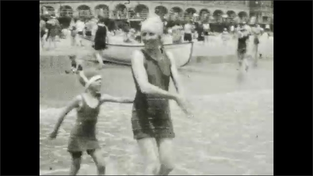 1930s: Man grabs women and plays on beach. Men, women and children stand and play in ocean.