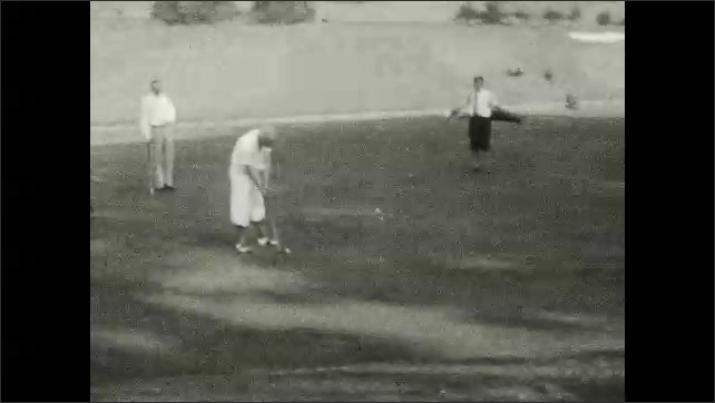 1930s: Tree-lined area near golf course. Man walks up stairs at country club. Men play golf on course. Men sit on bench near country club.