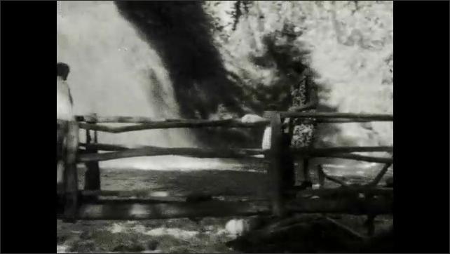 1920s: Waterfall.  Women and children cross bridges and climb stairs.