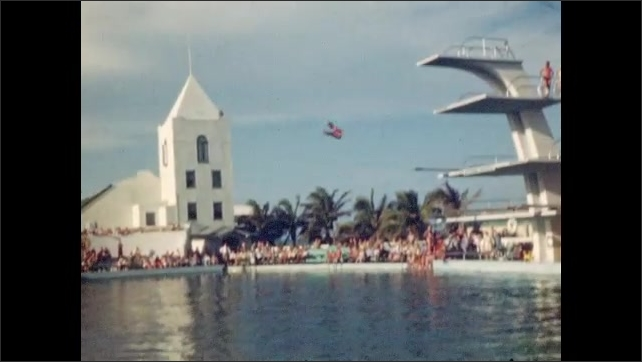 1940s: Woman dives badly, splashes. Crowd watches. Woman runs, jumps off diving board, does somersault. Man dives off high platform. Two women dive in sync. Man dives, twists, off high platform.