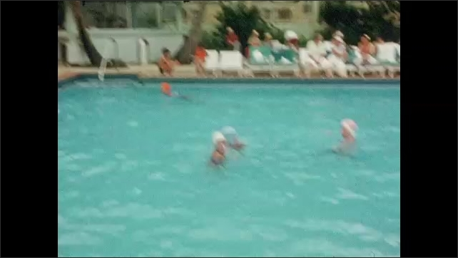 1940s: Girl speaks and jumps into swimming pool. Kids swim and play in pool. Girl swims to edge of pool.