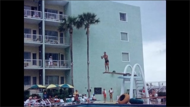 1940s: Men dive acrobatically off diving board. Man hangs on diving board. Men dive off board together into pool. Woman in hat speaks into microphone. Woman models swimwear at poolside.