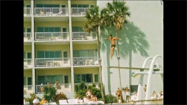 1940s: Men dive acrobatically into pool. Man swims backward holding barbell. Boy swims in pool.