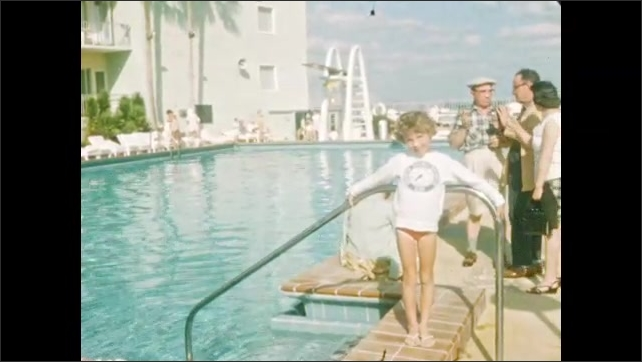 1940s: Men dive acrobatically into pool. Child poses near swimming pool. Men and children near swimming pool. Girl in dress walks down stairs.