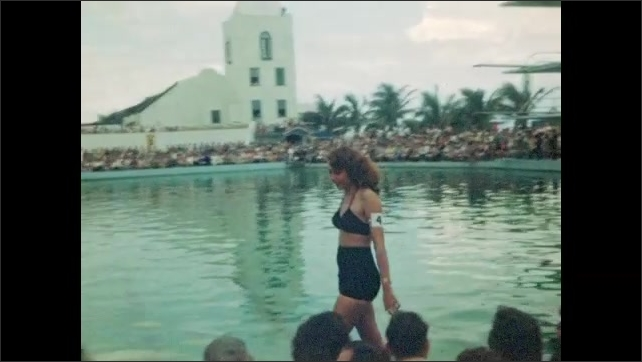 1940s: Beauty pageant, women wearing swimsuits and numbered armbands walk around perimeter of pool, smile. Large crowd watches.