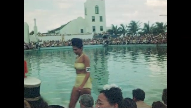 1940s: Beauty pageant, women wearing swimsuits and numbered armbands walk around perimeter of pool, smile. Large crowd watches. Man dressed in drag walks behind woman.