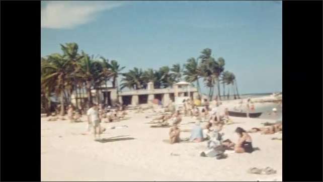1940s: Fully clothed older people under palms on beach. Panorama of people on sunny, tropical , sandy beach. Young women in bathing suits on towels on the beach.