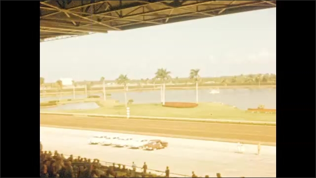 1940s: Exterior horse racetrack and water feature. Stands with crowds. Boats on water feature.