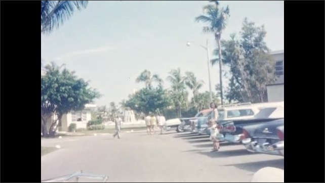 1940s: Girl walks out of door onto outdoor walkway, smiles. Car drives through parking lot.