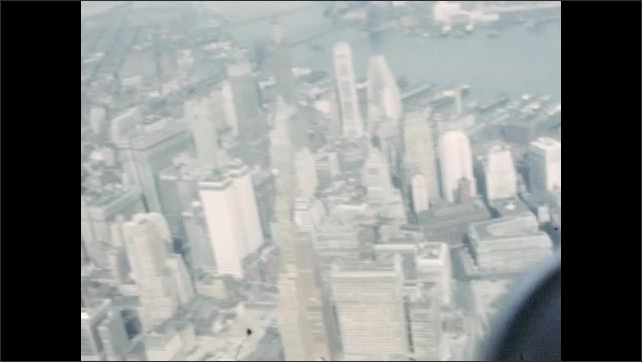 1940s: UNITED STATES: city and buildings seen from above. Bridge across river