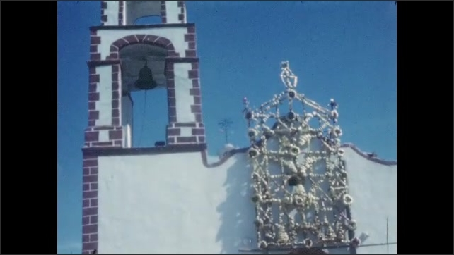 1940s: MEXICO: white church by road. Tower and bell on church. Decoration and architecture on church. Church wall.