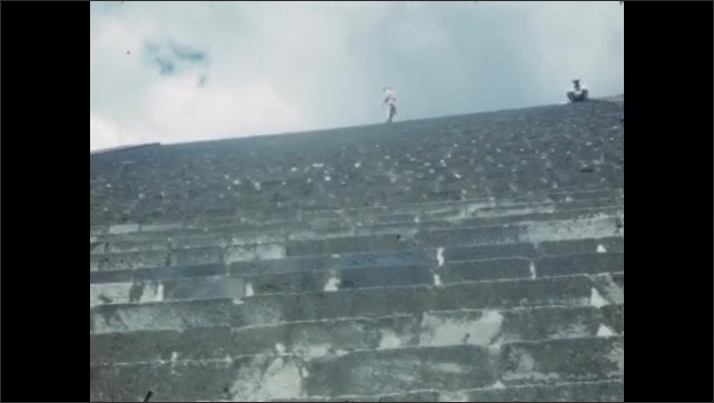 1940s: MEXICO: boy waves at camera from steps. Boy walks up side of rock building. Man stands on balcony