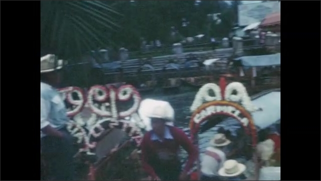 1940s: Man with glasses holds flowers, smiles and talks. Boy holds flowers, puts finger on his nose, sneezes. Trajineras on canal. Man and woman paddle boat, several boats stand on canal. Trajineras.