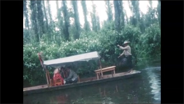 1940s: Man stands and paddles boat with flowers. Trajinera with tourists, man waves. Trajinera with people. Trajineiras on canal surrounded by trees. Two men stand on boats with flowers.