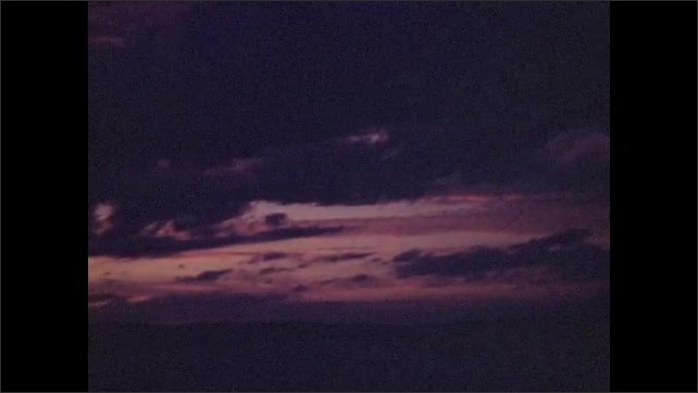 1940s: UNITED STATES: man rows boat on water as sun sets in sky. Clouds at sunset. Colorful dusk sky