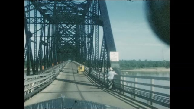 1940s: UNITED STATES: car drives across bridge. View of road through car window. Bridge over river. Barrier by roadside