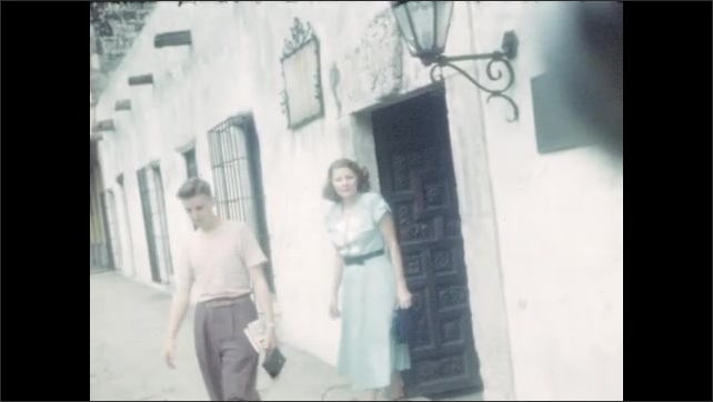1940s: View from car, driving in rain. Cars in parking lot. Boy and woman exit building. Boy in doorway by courtyard. Pan across courtyard. Boy and woman next to fountain.