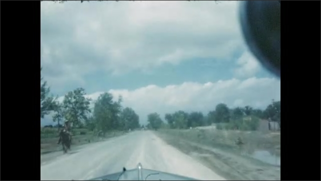 1940s: Shots from moving car, driving down road. View of town. Passing men with truck on side of road. Passing man on horseback. Views of town, pulling into parking space.