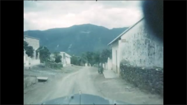 1940s: Shots from moving car, driving down road. Views of driving through town.