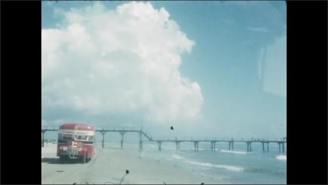 1940s: MEXICO: pier by beach. Coach drives along beach. View along beach. Bus drives under pier. Clouds in sky