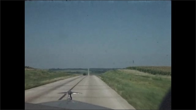 1940s: Car driving down open rural highway.