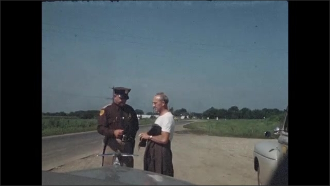 1940s: Man talks to police officer on the side of the road.