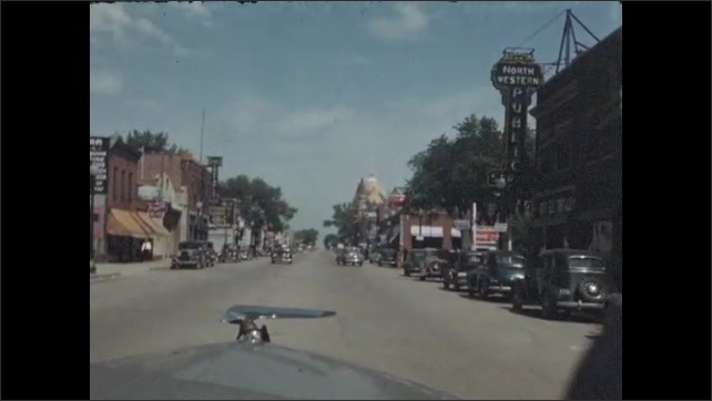 1940s: Car comes to fork in the road and goes left. Car drives through small town. Boys point at something on the wall in dark room.