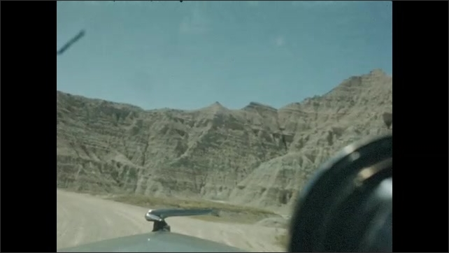 1940s: Car driving on long and winding road near desert cliffs.