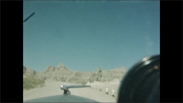 1940s: Car driving through desert on long road.