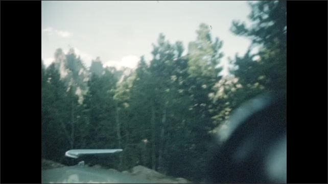 1940s: Car drives down wooded mountain road. Car drives toward rock spires. Car drives past large rock formations.