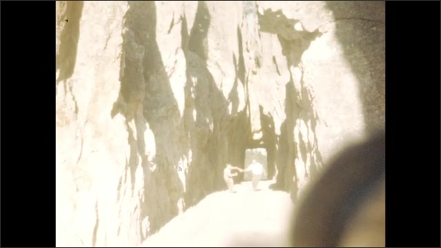 1940s: Mountains and road. Shadows fall across large rock formation. Man and boy hold hands and run through tunnel. Boy climbs on bricked tunnel opening. Boy straddles rocks.