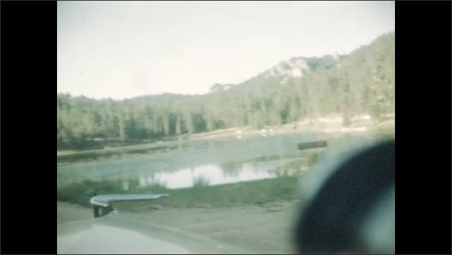1940s: Car drives along wooded road. Car drives up mountain road. Car drives past large lake.