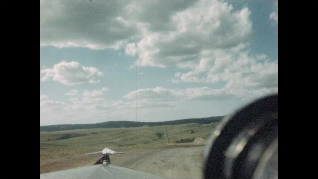 1940s: Car drives along rural road. Car drives through hills.