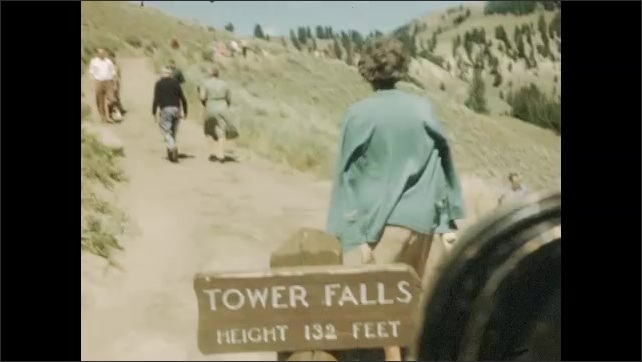 1940s: Car drives down curvy road. Sign for Tower Falls. People walk on dirt path. Waterfall.