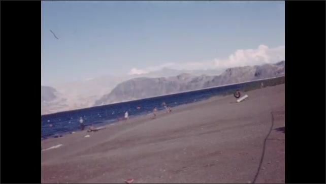 1940s: Large lake in desert. People play and walk on beach by lake.