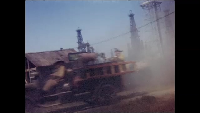 1940s: Antique fire truck drives by car parked in front of oil field. Woman stands in car, watches fire trucks pass by. Men walk up to car, look around, woman sits in car.