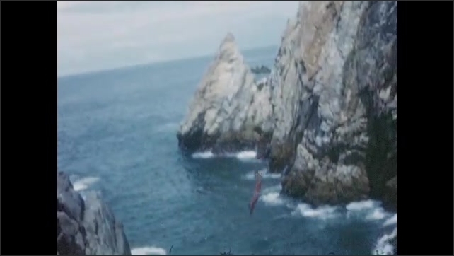 1940s: Mexico: boy dives into sea from cliff top. Boy swims in sea