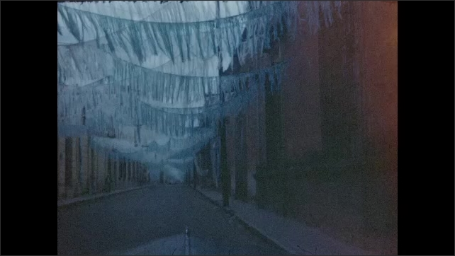 1940s: Car drives on a two-lane rural road up and down hills. Sky is blue and stormy. Car enters small town. Fringed banners crisscross above the street. Low-rise buildings and cars.