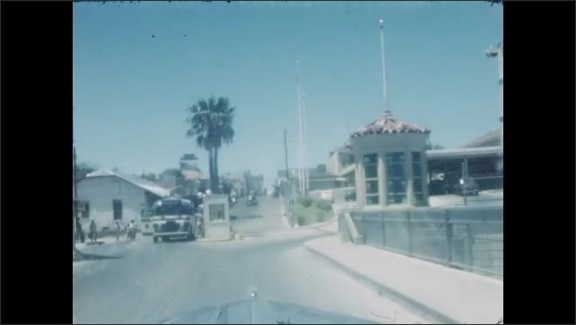 Car enters border of United States and Mexico. Cathedral style stone building and river. Uniformed officer inspects cars.