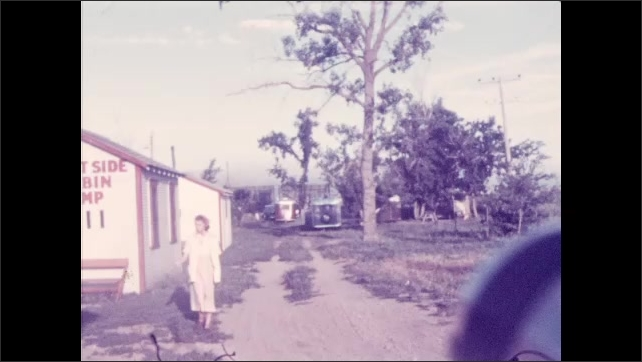 "1930s: A girl walks on a dirt path. Girl walks next to house with text ""West Side Cabin Camp"", tree in background. Four girls stand next to car with parked trailers in background."
